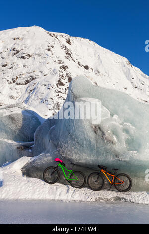 Fatbikes, 907 fat tire bike and Fatback fat tire bike, resting against giant iceberg in winter on Portage Lake, Chugach National Forest - Stock Photo