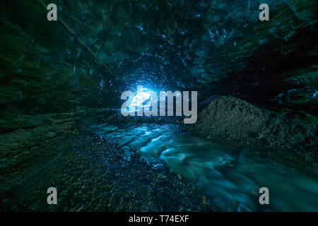 Looking toward the entrance of an ice cave while being 500 metres under a glacier; Iceland - Stock Photo