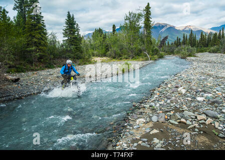 A man fat biking across a stream in Wrangell-St. Elias National Park and Preserve on a cloudy summer day in South-central Alaska - Stock Photo