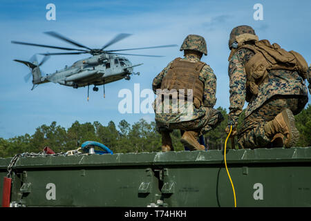 U.S. Marines with Landing Support Company, 2nd Transportation Support Battalion, Combat Logistics Regiment 2, prepare to lift a medium girder bridge at Camp Lejeune, North Carolina, May 2, 2019. 2nd TSB and Marine Heavy Helicopter Squadron 464 worked together to lift and move a medium girder bridge with a CH-53E Super Stallion to improve operational capabilities. (U.S. Marine Corps photo by Cpl. Damion Hatch Jr.) - Stock Photo