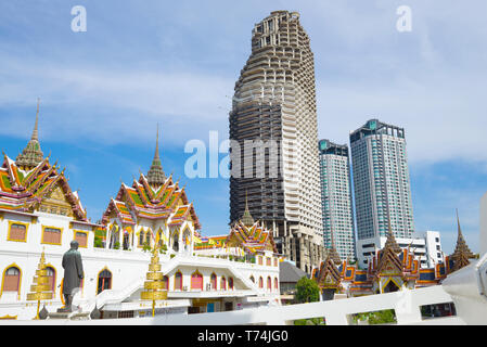 View of the abandoned skyscraper of Sathorn Unique Tower from the Buddhist temple Wat Yannava - Stock Photo