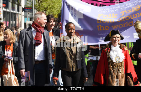 Brighton UK 4th May 2019 - Rokia Traore (centre) leads thousands of schoolchildren , teachers and parents taking part in the annual Brighton Festival Children's Parade through the city which has the theme 'Folk Tales from Around the World' . Organised by the Same Sky arts group the parade traditionally kicks off the 3 week arts festival with this years guest director being the singer songwriter Rokia Traore . Credit : Simon Dack / Alamy Live News - Stock Photo