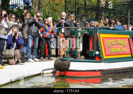London, UK. 4th May, 2019. Spectators watch decorated narrowboats as they take part in the IWA Canalway Cavalcade Festival opening ceremony and pageant along the canalways and in the basin. The popular festivities are organised by the Inland Waterways Association and will run 4-6th May and will feature more than 100 boats this year with canal boat pageants, an illuminated boat parade, music, stage performances and water sports along pool and Grand Union Canal in Little Venice.Little Venice, London, UK, 4th May 2019. Credit: Imageplotter/Alamy Live News - Stock Photo