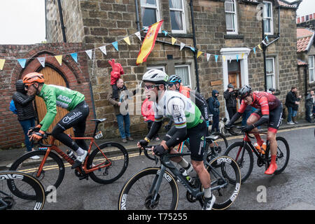 Grrosmont, North Yorkshire, England, UK. 4th May 2019. Weather: Gruelling conditions in the mens race at the Tour de Yorkshire as riders (including Mark Cavendish, centre) tackle the steep 1in3 climb out of Grosmont on a cold, wet and very windy Saturday in North Yorkshire. Heavy hail and rain showers along the route also made for difficult riding conditions. Credit: Alan Dawson/Alamy Live News. - Stock Photo