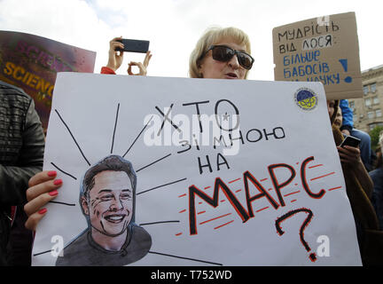 Kiev, Ukraine. 4th May, 2019. A woman holds a poster with an image of CEO of SpaceX and Tesla Motors Inc. Elon Musk and reading like 'Who is with me on Mars?' during costumed March For Science in center of Kiev, Ukraine, on 4 May 2019. Popularizers of science, physicists and adherents of science took part in the 'March For Science' global action for the liberty of research and teaching, during rallies which took place around the world on Saturday on May 4. Credit: Serg Glovny/ZUMA Wire/Alamy Live News - Stock Photo