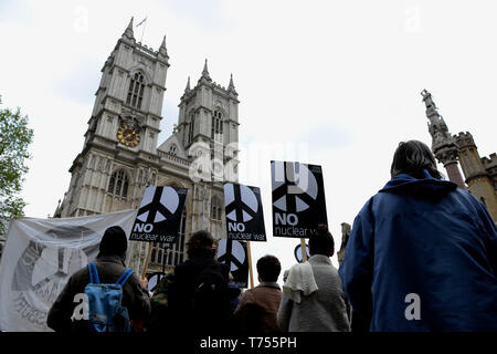 """Activist are seen holding placards during the protest. Anti-nuclear activists gathered opposite Westminster Abbey in London to protest against a service of thanksgiving organised by The Royal Navy to mark 50 years of Britain's submarine-based nuclear weapons. Anti-nuclear activists performed a """"die-in"""" outside Westminster Abbey representing the victims of nuclear war. - Stock Photo"""