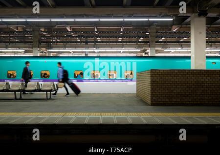 Travellers boarding the Hayabusa E5 Shinkansen at Yamagata Station, Japan. - Stock Photo
