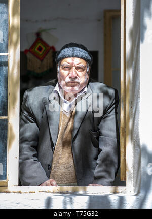 kashan, Iran, 25th April 2019: iranian man looking out of his window in a village in Iran - Stock Photo