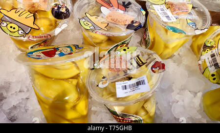 Saigon/Vietnam: 1 Apr 2019: Delicious yellow mango slices with salt chillies spicy dipping sauce Vietnamese street food on shelf with ice cubes - Stock Photo