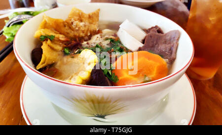 Delicious vegetarian food corn carrot tofu mushroom fungus rice noodles soup spring onion crispy rice paper in white bowl wooden table lemon tea ice - Stock Photo