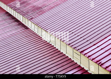 Detail view of a roof made of red colored metal sheets. A diagonal overhang gives a 3-dimensional impression. - Stock Photo