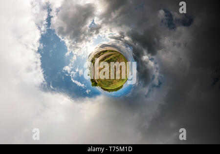 Little planet spherical panorama 360 degrees. Spherical aerial view in field in nice day with awesome clouds. Curvature of space. light vs darkness - Stock Photo