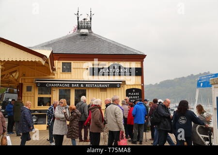 Tourists are waiting for the ferry near Platform 1, a champagne bar & restaurant in Dartmouth harbour, Devon, UK - Stock Photo