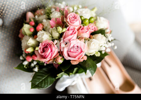 Wedding bouquet of white and pink roses on a blurred background of the bride's shoes - Stock Photo