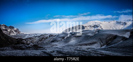 Huge majestic glacier's icy surface by snowy mountain in Iceland - Stock Photo