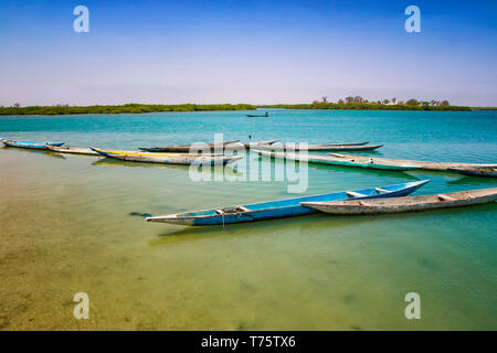 Wooden canoe on sea lagoon in Senegal in Africa. It is the Saloum National Nature Park, a bird sanctuary. In the background is blue sky and the island - Stock Photo