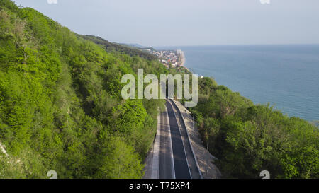Aerial view over mountain road going through forest landscape, Winding road from high mountain pass.