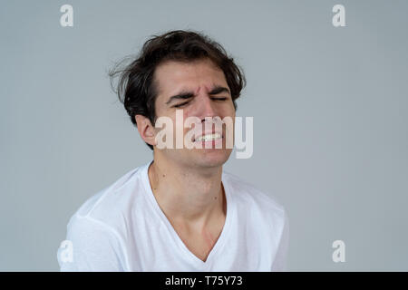 Young man feeling confused and displeased staring in disgust. Looking puzzled not understanding or liking something. Portrait with copy space. In Peop - Stock Photo