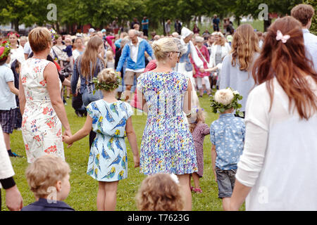 Mariefred, Sweden - June 24, 2016: People participate in the public traditional celebration of the midsummer holiday dancing around the midsummer pole - Stock Photo