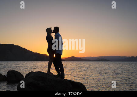 Gentle kiss on the background of the sunset. Silhouette of a kissing couple by the sea. Romance Summer Vacation - Stock Photo