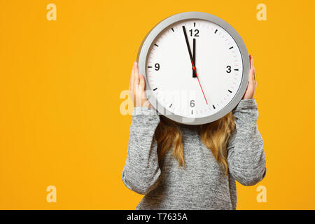 Little child girl holding a big clock on a yellow background. The concept of education, development, school, time management, deadline, time to learn. - Stock Photo