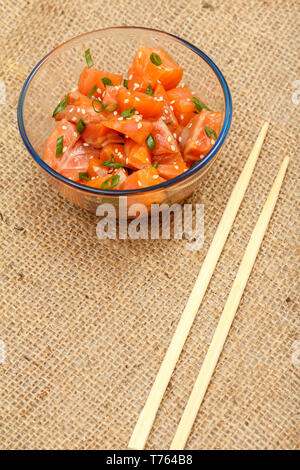 Hawaiian salmon poke with green onions and sesame seeds in glass bowl with chopsticks on sackcloth. Top view. Organic seafood. - Stock Photo