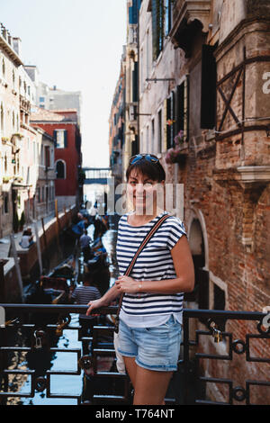 Young woman tourist standing on a bridge near rio del Vin canal in Venice, Italy. Travel concept. - Stock Photo