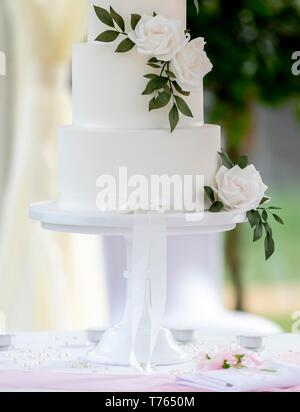 Close up of elegant minimalist wedding cake decorated with white roses on a table in a traditional summer marquee. - Stock Photo
