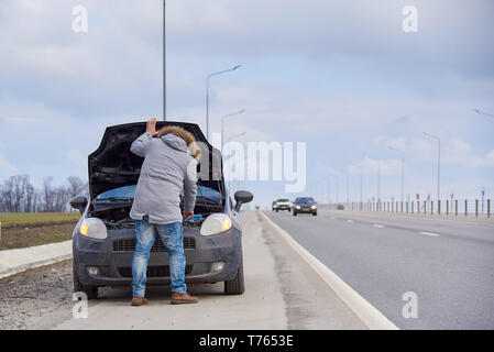 A young man near car with an open hood on the roadside. - Stock Photo