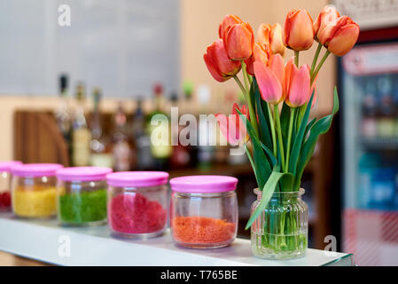 A bouquet of tulips in a vase on the bar counter. - Stock Photo