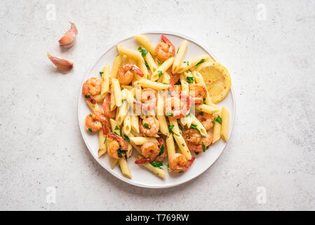 Penne Pasta with Prawns or Shrimps, lemon and garlic on white, top view, copy space. Lemon pasta with sauteed shrimps, fresh seafood. - Stock Photo