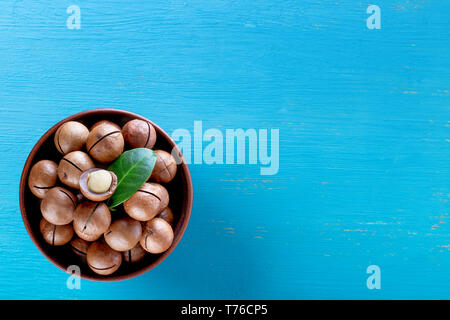 Australian macadamia nuts with leaf in the plate on blue wooden background - Stock Photo