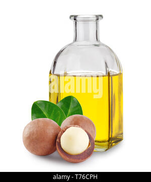 Macadamia oil in a glass bottle and nuts with leaves isolated on white background - Stock Photo