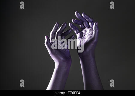 Female hands dyed in purple color on dark background - Stock Photo