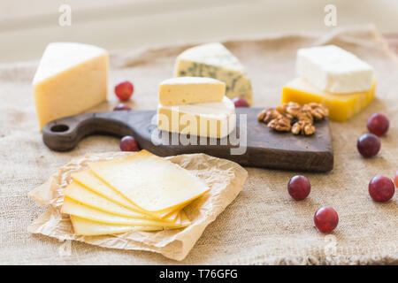 Cheese party table, perfect holiday appetizer with nut on rustic wooden board - Stock Photo