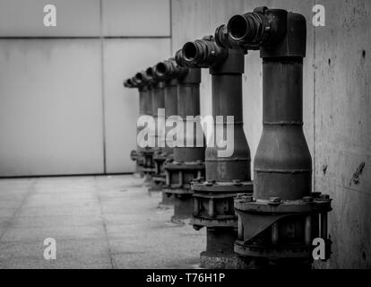 Fire safety pump on cement floor of concrete building. Deluge system of firefighting system. Plumbing fire protection. Fire pump in front of concrete  - Stock Photo