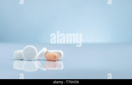 Pharmacy drugstore product. Pile of orange and white tablets pill on gradient background. Different size and shape tablets pills. Pharmaceutical - Stock Photo