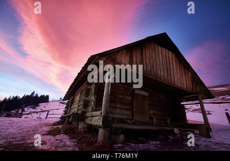 The mountain covered with snow beautiful cover rests on top of the house and the shepherds to summer grazing sheep and spend the night there in the wi - Stock Photo