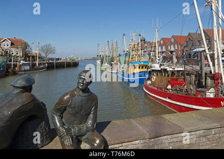 statues of old fisherman and young fisherman, fishing harbour, Neuharlingersiel, East Friesland, Lower Saxony, Germany - Stock Photo