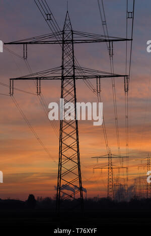 Silhouette of high voltage power lines and pylons leading to a steam power station in front of a colorful after sunset sky. Karlsruhe, Germany - Stock Photo