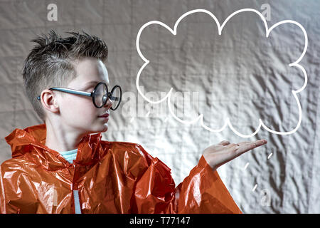 a boy in a bright orange raincoat and round glasses on his palm holding a painted cloud, where you can enter the text - Stock Photo