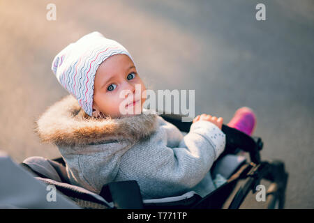 The little girl turns back sitting in a baby carriage on a walk in the park. Autumn season clothes. Warm childrens wear - Stock Photo