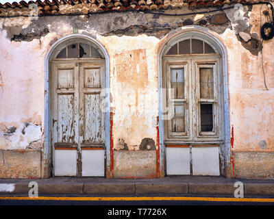 Front view of an old, dilapidated and rundown old town house in 'San Sebastian' on 'La Gomera' (Canary Island). crumbling plaster - Stock Photo