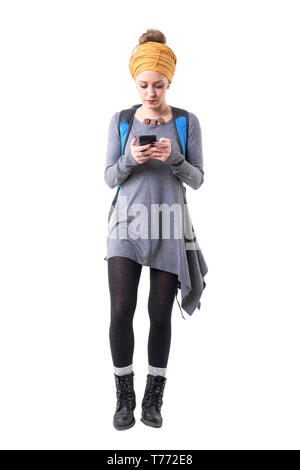 Young tourist hipster woman walking and looking at mobile phone map navigation. Full body isolated on white background. - Stock Photo