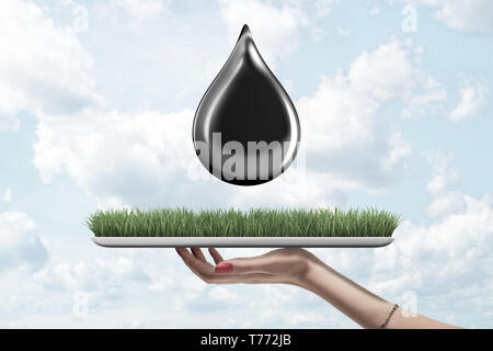 Female hand holding green grass board with black oil drop on blue sky background - Stock Photo