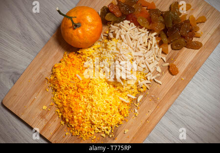 Dried raisin, chopped almonds and crushed mandarin shells on wooden board over grey wooden background, top view. Close-up. - Stock Photo