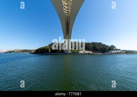 underneath the modern concrete Ponte da Arrabida bridge in Porto, Portugal, spanning the Rio Douro. - Stock Photo
