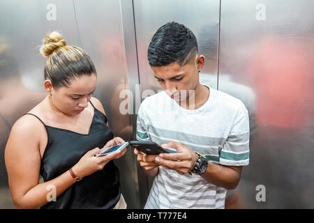 Cartagena Colombia El Laguito Hotel Dann Cartagena hotel inside Hispanic resident residents teen boy girl elevator riding looking at smartphone textin - Stock Photo