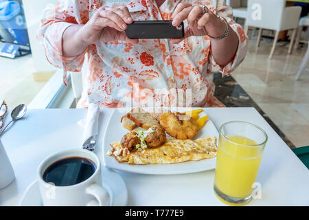 Cartagena Colombia El Laguito Hotel Dann Cartagena hotel restaurant free included breakfast buffet plate omelet meatballs rolls bread orange juice cof - Stock Photo
