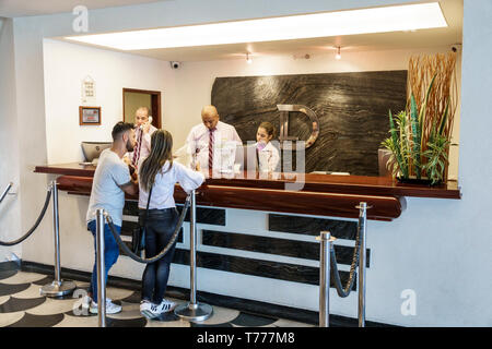 Cartagena Colombia El Laguito Hotel Dann Cartagena hotel inside Hispanic resident residents man woman front desk reception reservation clerk working e - Stock Photo